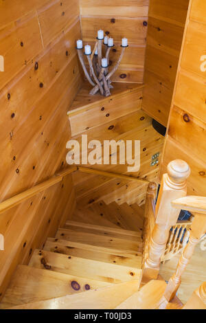 Pinewood staircase leading to downstairs floor from upstairs floor inside a piece sur piece Eastern white pine log and timber home - Stock Image