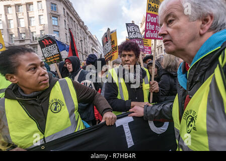 London, UK. 9th Dec, 2018. A united counter demonstration by anti-fascists has to wait for a few minutes on Haymarket until police clear the route. The protest was in opposition to Tommy Robinson's fascist pro-Brexit march. The march which included both remain and leave supporting anti-fascists gathered at the BBC to to to a rally at Downing St. Police had issued conditions on both events designed to keep the two groups well apart. Credit: Peter Marshall/Alamy Live News - Stock Image