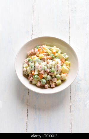 Traditional russian salad 'Olivier' from boiled vegetables and sausage with mayonnaise in bowl. Russian New Year or Christmas salad on light wooden ba - Stock Image