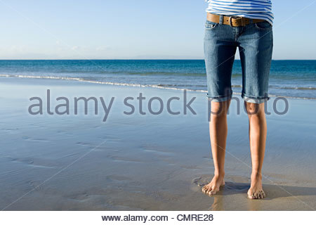 Woman standing by the sea - Stock Image