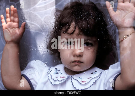 Baby Girls behind glasses with rain - Stock Image