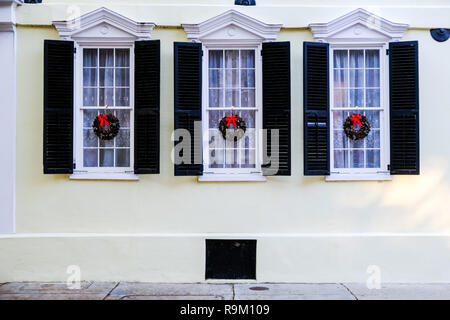 Christmas holiday wreaths decorate windows on a historic home during the holidays along Tradd Street in Charleston, South Carolina. - Stock Image