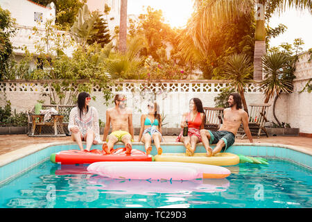 Group of happy friends relaxing in swimming pool - Young people having fun in exclusive summer tropical vacation - Stock Image