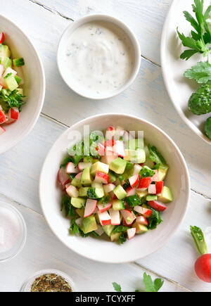 Vegetable salad from avocado, radish, cucumber, greens in bowl over light wooden background. Organic natural or vegetarian vegan food concept. Top vie - Stock Image