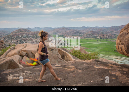 Girl performing poi on a mountain at sunset. - Stock Image