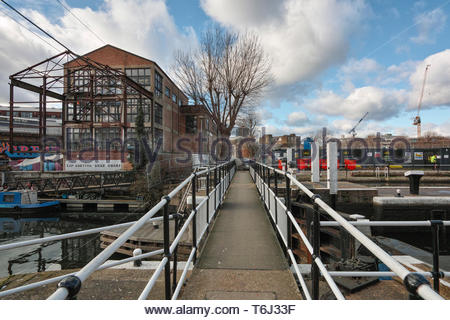 The footpath across Old Ford Lock to the Swan Wharf building on FIsh Island and Hackney Wick: London. - Stock Image