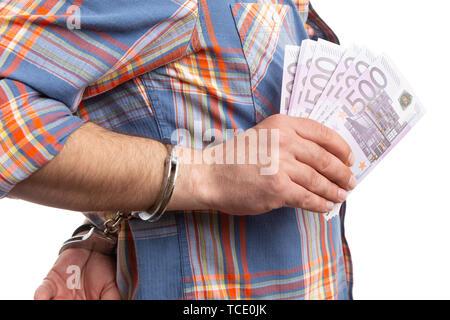 Corrupted man presenting bribe money with handcuffed hands closeup isolated on white studio background - Stock Image