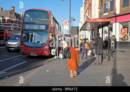 People getting on a 432 bus and passengers waiting at a bus stop on Brixton Road in Brixton South London SW9 England UK  KATHY DEWITT - Stock Image