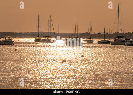Poole, UK. 28th June 2018. UK weather. The sun sets over Poole Harbour on one of the hottest days on record. Boats moored. Credit Thomas Faull / Alamy Live News - Stock Image