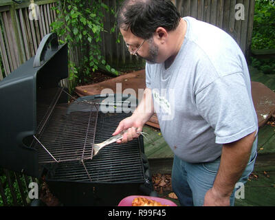 man cleaning grill - Stock Image