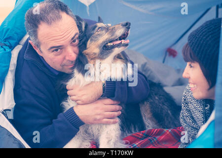Love and friendship concept with man and woman and pretty adorable collie dog hugged from the owner - blue colors and outdoor leisure activity for peo - Stock Image