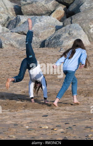 Young teenage girls doing handstands on Fistral Beach in Newquay Cornwall. - Stock Image
