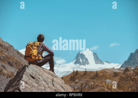 Man hiker with backpack sits on big rock and looks at white mountain with glacier - Stock Image