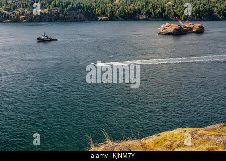 Tugboat towing ITB Beaufort Sea, barge loaded with timber, Seymour Narrows at Discovery Passage, Vancouver Island - Stock Image
