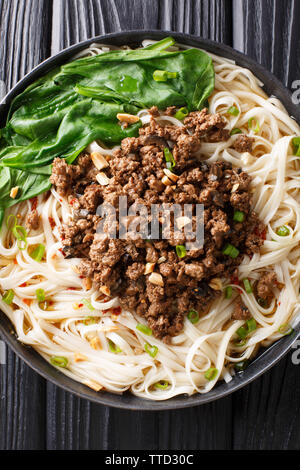 Dan Dan Noodles - Savory and spicy Sichuan noodles served with ground meat closeup on the plate on the table. Vertical top view from above - Stock Image