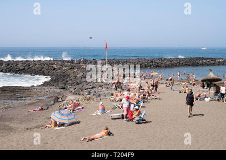 People sunbathing on the beach at Costa Adeje, Tenerife, Canary Islands. - Stock Image