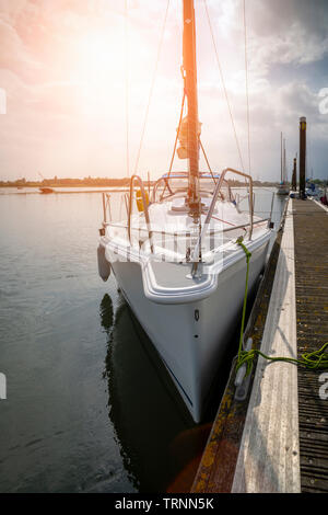 Sailing yacht moored on a wooden pontoon in a tranquil harbour as the sun sets, viewed from the bow. - Stock Image