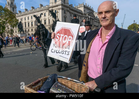 London, UK. 13th October 2018. Donnachadh McCarthy of Stop Killing Cyclists at the head of the funeral procession of cyclists behind a horse-drawn hearse to highlight the failure of governments from all the major parties to take comprehensive action on safer cycling. Stop Killing Cyclists call for £3 billion a year to be invested in a national protected cycling network and for urgent action to reduce the toxic air pollution from diesel and petrol vehicles which kills tens of thousands of people every year, and disables hundreds of thousands. The several hundred protesters staged a ten-minute d - Stock Image