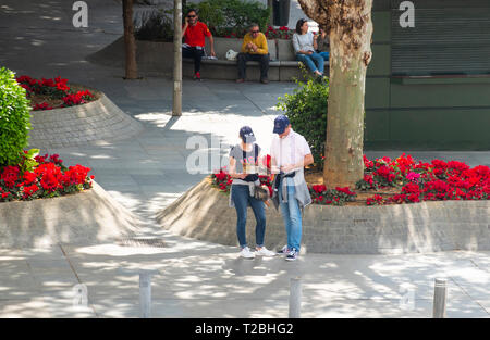 American tourists consulting both a paper map and a cellphone for directions - Stock Image