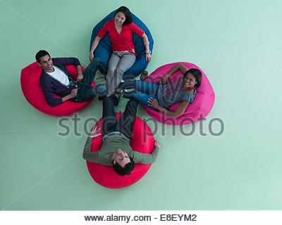 Smiling men and women  bean bag chairs - Stock Image