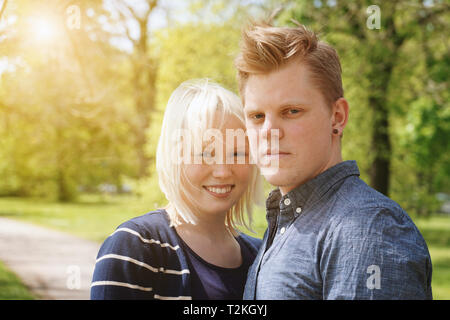 young couple enjoying sunny spring day in a park - real people with sun flare light leak filter - Stock Image