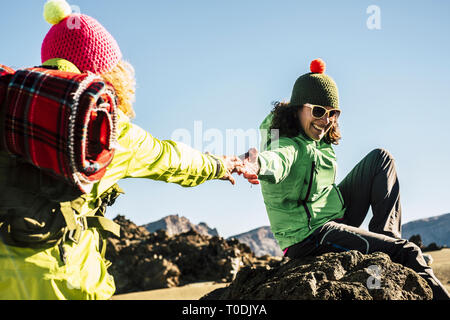 Couple of happy woman helping eachother to arrive to the top of the mountain - enjoy the outdoor trekking hiking activity - clear blue sky in backgrou - Stock Image
