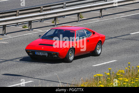 A classic red  Ferrari  Dino 308 or 208 GT4 driving  along the road - Stock Image