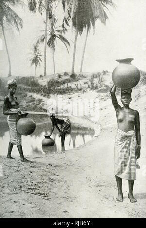 Tshi (or Tchwi, or Oji) women of Ghana (then part of the British Empire), West Africa, filling their water jars at a pool. - Stock Image