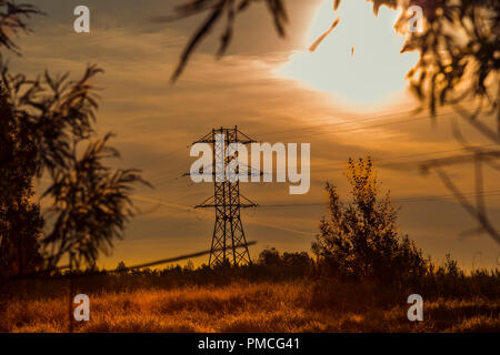 The setting sun illuminates with its beams a metal structure of the power line support - Stock Image