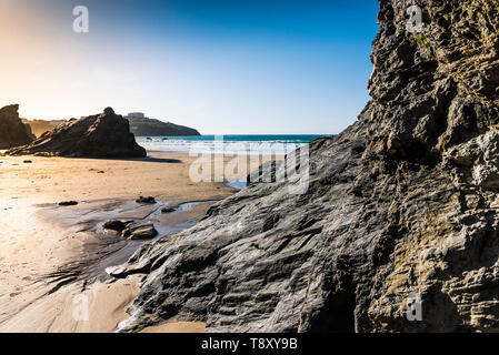 Evening light over rocks exposed at low tide on Great Western Beach in Newquay in Cornwall. - Stock Image