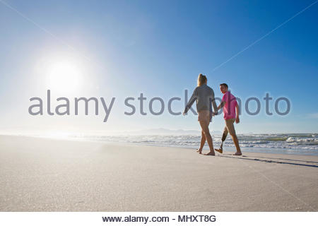 Low Angle Shot Of Man With Artificial Leg Walking Along Beach Holding Hands With Female Partner On Summer Vacation - Stock Image