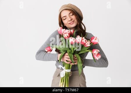 Photo of gorgeous woman 30s wearing hat holding bunch of beautiful flowers isolated over white background - Stock Image