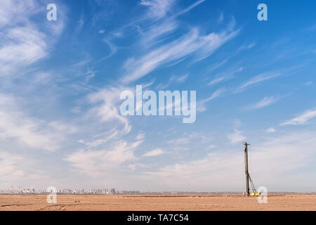Site ready for building construction. Panoramic landscape with sand, drilling machine and distant city - Stock Image