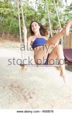 Young woman wearing blue bikini on swing at beach - Stock Image