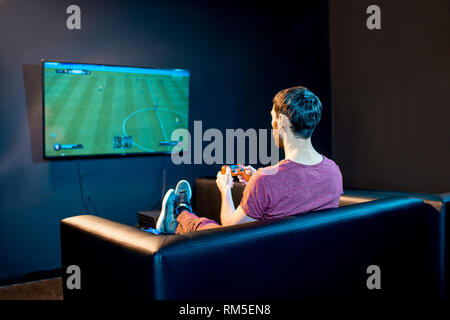 Man playing football game with gaming console sitting on the couch in front of the monitor at home or playing club - Stock Image