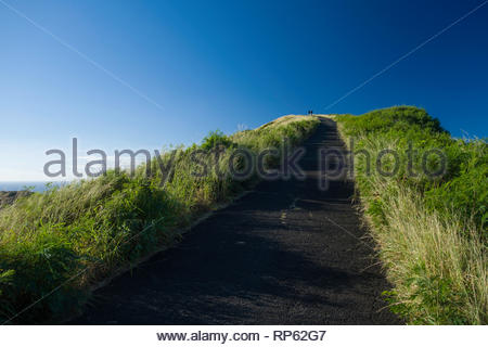 Two men walking up access road to the summit of Koko Head, Koko Head District Park, Hawaii Kai, Oahu, Hawaii, USA - Stock Image