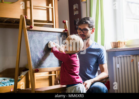 Little boy cleaning the blackboard while father is watching, Munich, Germany - Stock Image