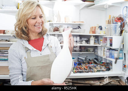 Mature Woman Holding Vase In Pottery Studio - Stock Image