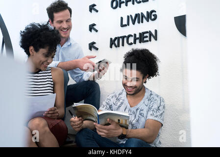People sitting together in stairwell talking - Stock Image