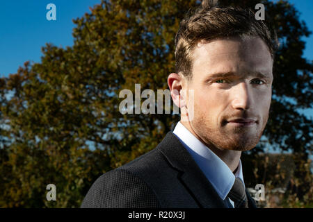Handsome man wearing a suit in countryside with trees and fields behind him - Stock Image