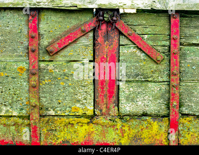 Red arrow-shaped fittings on a farm trailer - Stock Image
