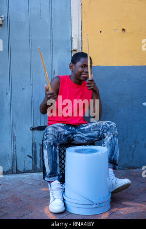 Young African-American street drummer boy drumming on a plastic bucket on Bourboun Street, New Orleans French Quarter New Orleans, Louisiana, USA - Stock Image