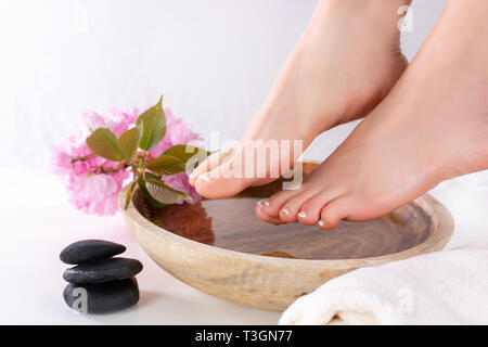 Girl feet with french pedicure in wooden bowl with water and decorative pink flower in beauty and spa studio. Female foot health and care concept - Stock Image