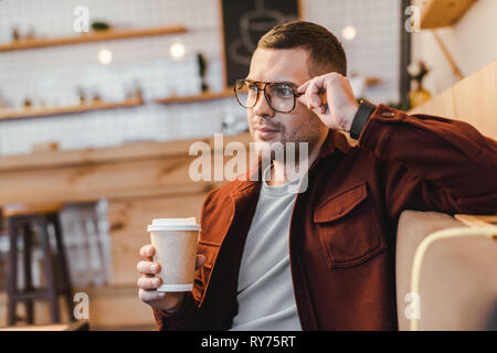 handsome man in burgundy shirt and black jeans sitting on couch and holding paper cup in coffee house - Stock Image