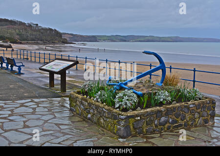 The beach at the seaside resort of Saundersfoot on a damp Winter's day. Old blue-painted anchor & flowerbed in foreground. Walkers on beach. - Stock Image