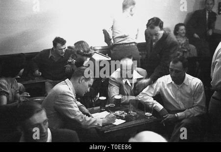 1950s, men and women socialising, siting and relaxing in a pub after work with a drink and cigarette, England, UK. - Stock Image