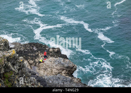 Anglers fishing from rocks on the coast of Newquay in Cornwall. - Stock Image