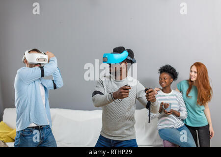 Multiethnic diverse friends enjoying VR technology, two guys wearing vr headset and playing while african and caucasian redhead girl look at them and  - Stock Image