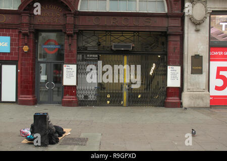 London, UK. 25th Dec, 2018: A homeless person seeps by a pillar outsde the Oxford Street exit on Christmas day with no public transport running on 25th December 2018. Some parts of the city experienced dense fog which is expected to linger for the rest of the week. Credit: David Mbiyu/Alamy Live News - Stock Image