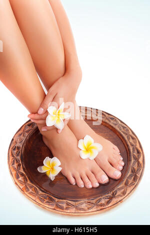 Beautiful womens legs and frangipani flowers over white blue background, beauty treatment, perfect skin waxing, - Stock Image